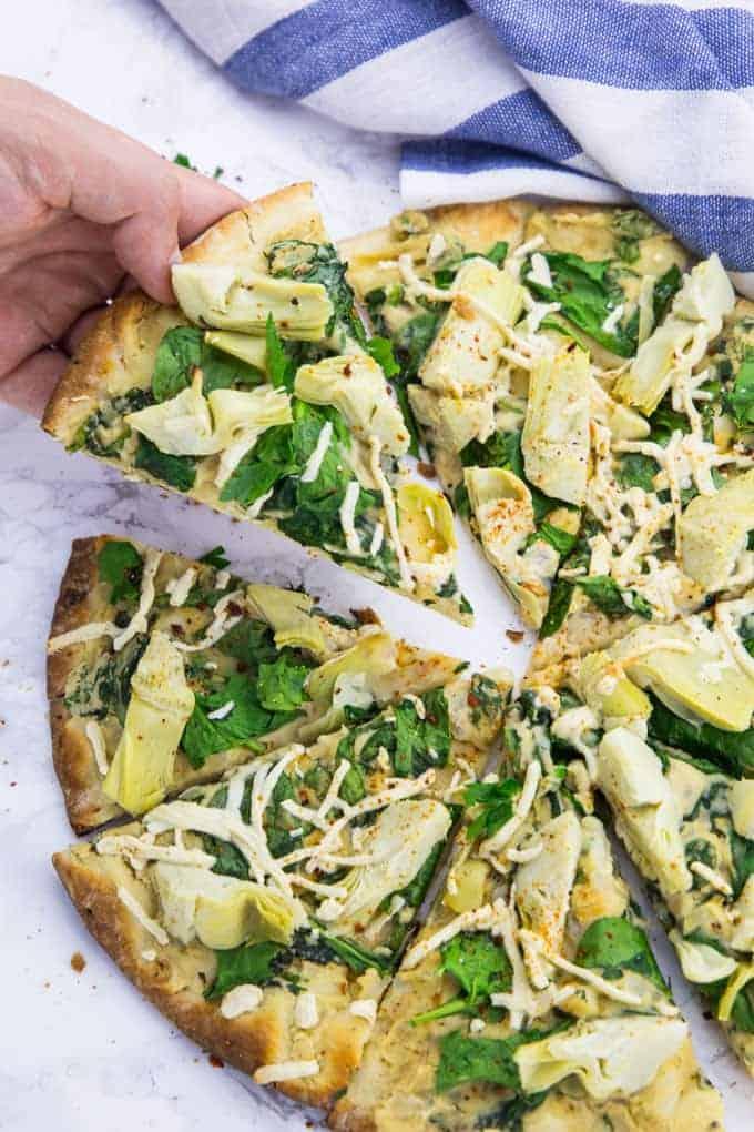 eine Hand nimmt ein Stück vegane Pizza, das auf einer Marmorplatte liegt