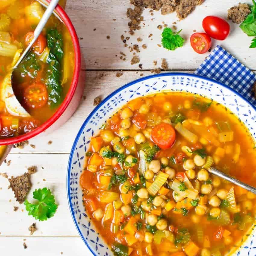 Italienische Kichererbsen Suppe in einem blauen Teller auf einem weißen Holzbrett mit einem Topf im Hintergrund