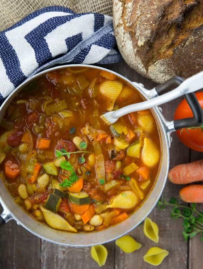 ein Topf mit Minestrone Suppe und einem Schöpflöffel auf einer Holzplatte mit einem Brot im Hintergrund