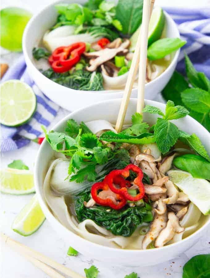 Pho Suppe in zwei weißen Schüsseln mit Stäbchen und Limetten