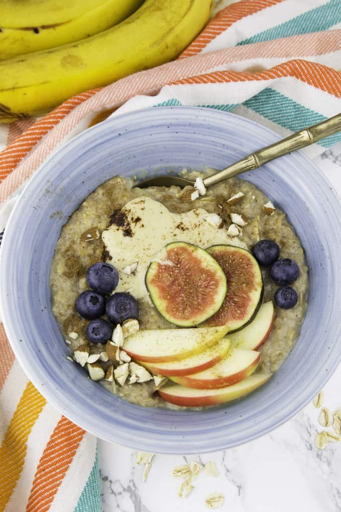 Porridge in einer blauen Schale mit Mandelmus, Zimt, Apfelscheiben, gehackten Mandeln und Blaubeeren auf einer Marmorplatte