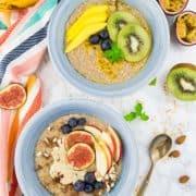 Porridge mit Obst in zwei blauen Schüsseln mit Löffeln auf einer Marmorarbeitsplatte mit einem bunten Tischtuch