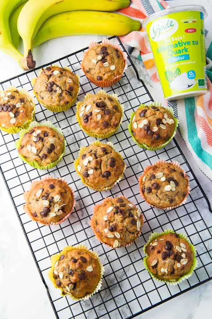12 Schoko Bananen Muffins auf einem Abkühlgitter mit Bananen und einem Becher veganem Quark im Hintergrund