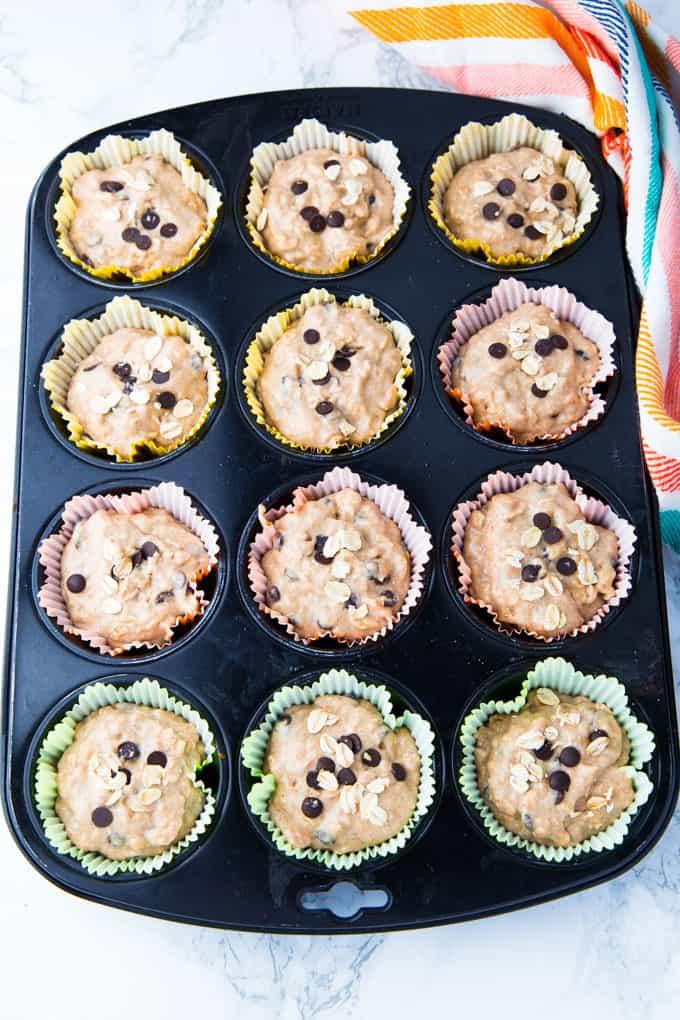 Schoko Bananen Muffins in Muffinförmchen in einem Muffinblech vor dem Backen