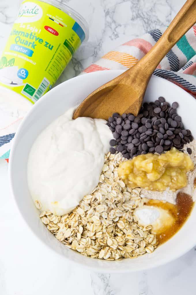 die Zutaten für Schoko Bananen Muffins in einer weißen Schüssel mit einem Holzlöffel