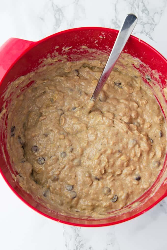 Teig für Schoko Bananen Muffins in einer roten Rührschüssel mit einem Löffel auf einer Marmorplatte
