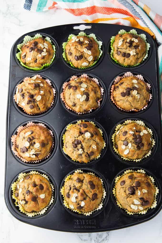 Schoko Bananen Muffins in einem Muffinblech auf einer Marmorplatte nach dem Backen