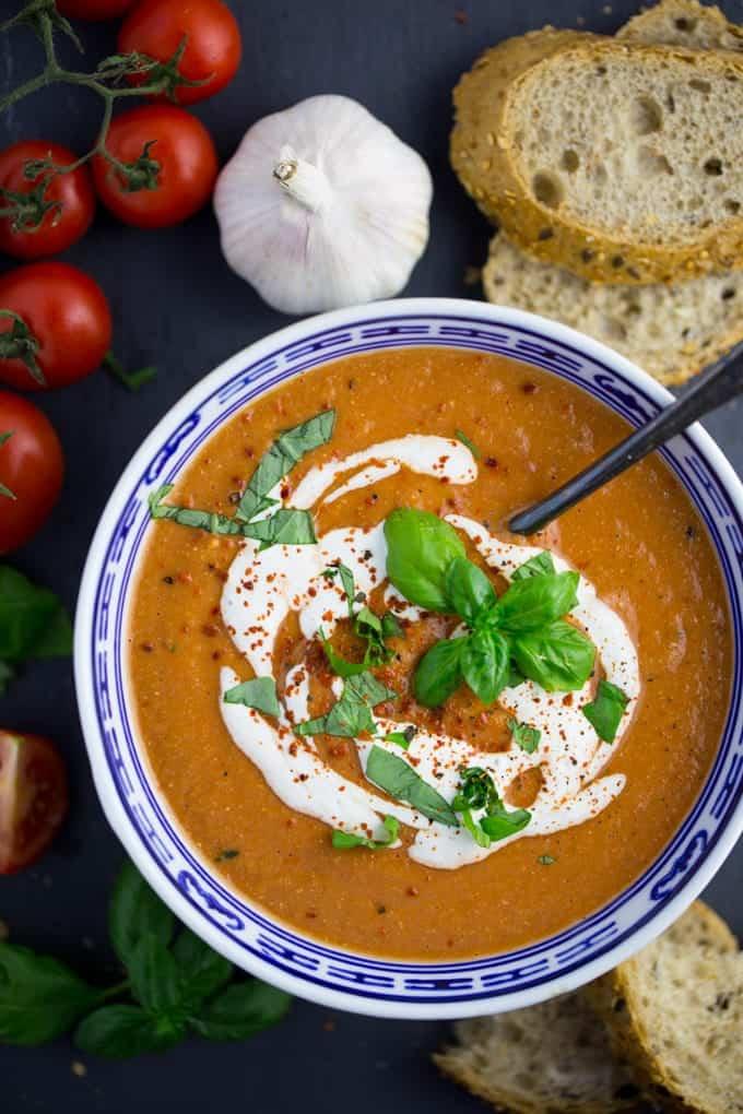 vegane Tomatensuppe in einer blauen Schale auf einem dunklen Untergrund mit frischem Brot, Kirschtomaten und einer Knoblauchzehe im Hintergrund