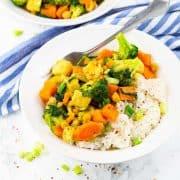 Gemüsecurry mit Reis in einem weißen Teller mit einer Gabel auf einer Marmorplatte mit einem blau weiß gestreiften Tischtuch im Hintergrund