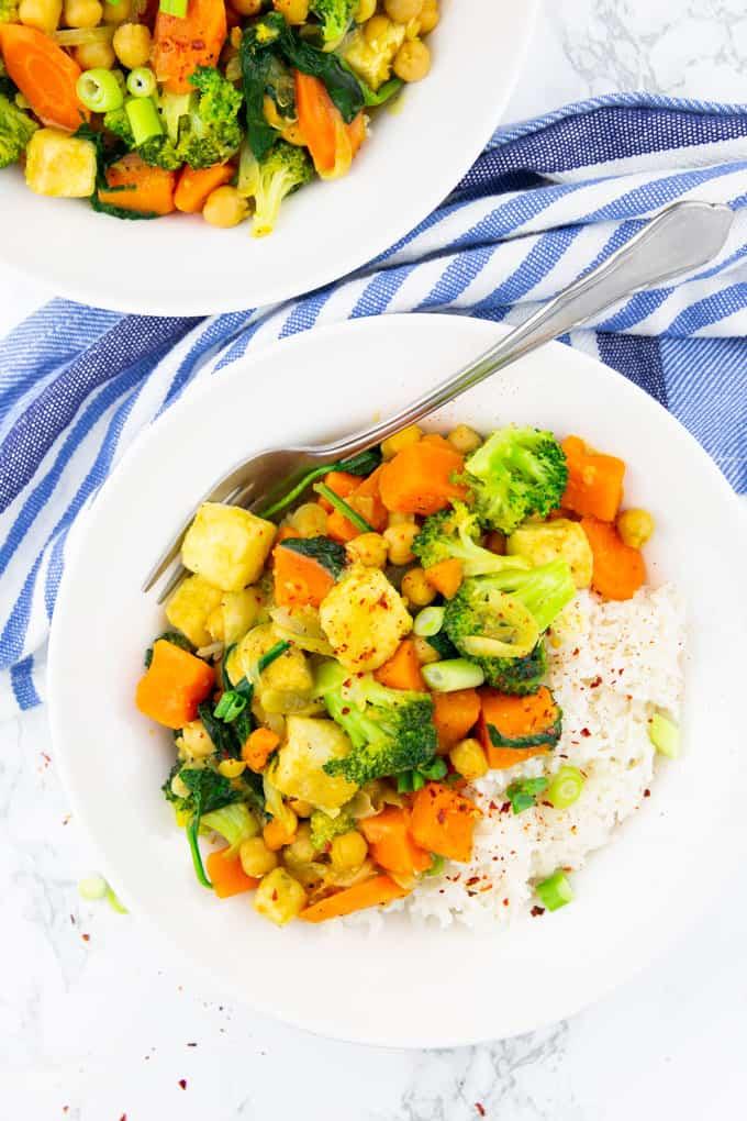 Gemüsecurry mit Basmati Reis in einem weißen Teller mit Gabel auf einer Marmorplatte mit einem zweiten Teller im Hintergrund