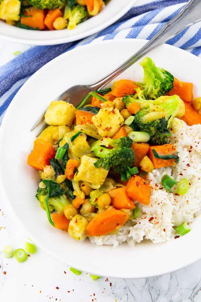 Gemüsecurry mit Basmati Reis in einem weißen Teller mit Gabel auf einer Marmorplatte mit einem blauen Geschirrtuch im Hintergrund