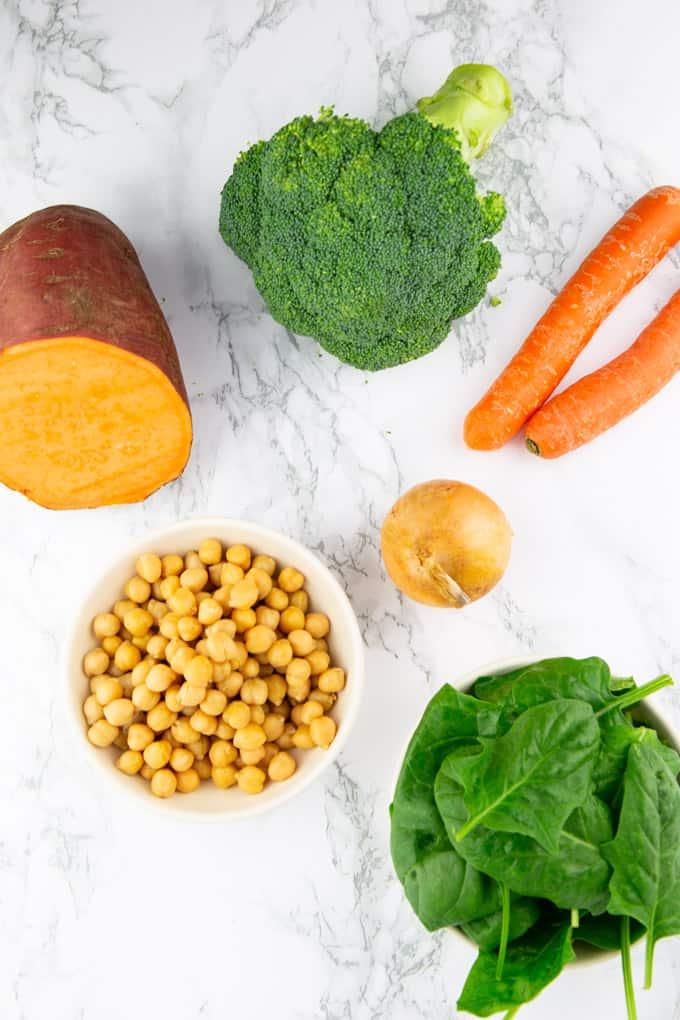 eine halbe Süßkartoffel, eine Zwiebel, zwei Karotten, ein Broccoli sowie zwei Schälchen mit Spinat und Kichererbsen auf einer Marmorplatte