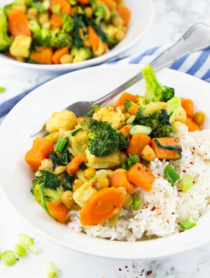 Gemüsecurry mit Reis in einem weißen Teller mit einer Gabel auf einer Marmorplatte mit einem zweiten Teller mit Curry im Hintergrund