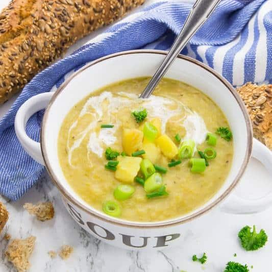 """Kartoffelsuppe in einer weißen Suppenschale mit der Aufschrift """"Soup"""" auf einer Marmorplatte mit einem Löffel, Kräutern und Brot im Hintergrund"""
