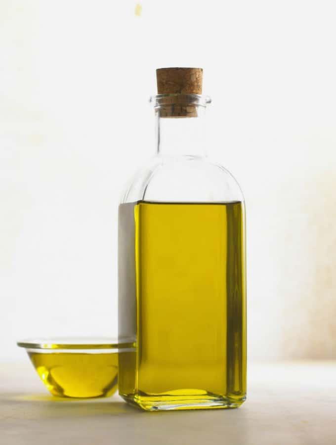 Öl in einer Glasflasche mit einem kleinen Glasschälchen mit Öl neben der Flasche