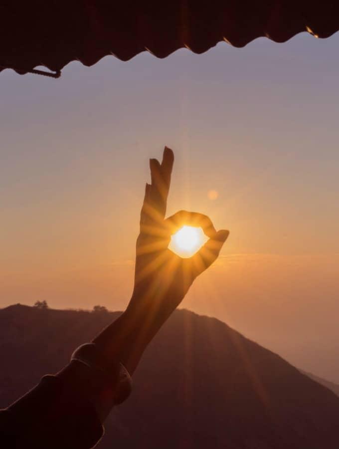 eine Hand, die die Sonne bei Sonnenuntergang umschließt