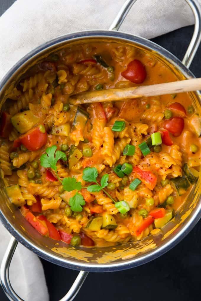 Vegane One Pot Pasta mit Kokosmilch und roter Currypaste in einem silbernen Topf auf einer schwarzen Platte