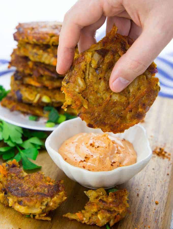 eine Hand, die einen Kartoffelpuffer in eine kleine Schüssel mit Sriracha Mayonnaise taucht mit mehr Kartoffelpuffer auf einem Teller im Hintergrund