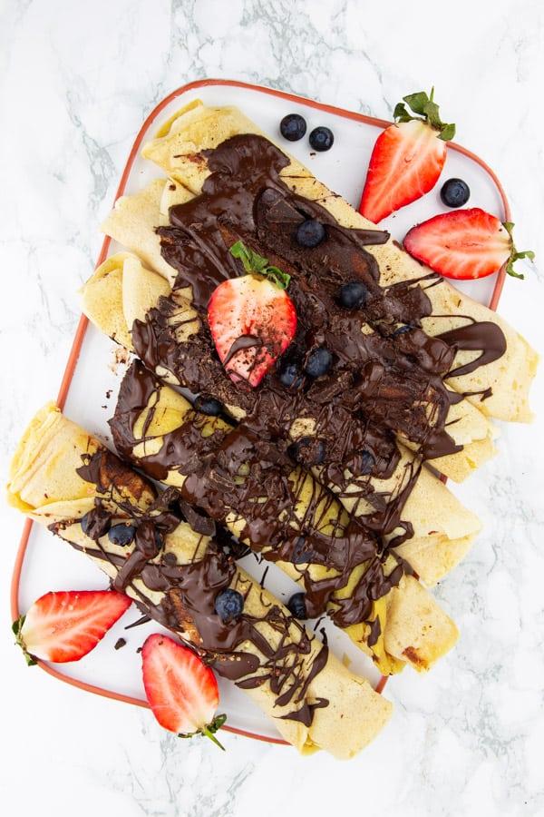 vegane Pfannkuchen auf einem weißen Teller mit Schokoladensauce, Erdbeeren und Blaubeeren auf einer Marmorplatte