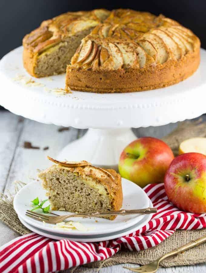 veganer Apfelkuchen auf einer weißen Kuchenplatte mit einem Stück Kuchen auf einem Teller mit Gabel im Vordergrund