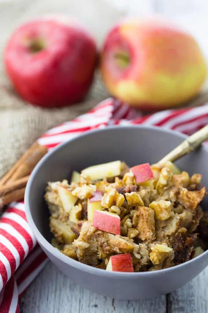 Slow Cooker Oats mit Quinoa, Apfel und Zimt in einer grauen Schüssel mit zwei Äpfeln im Hintergrund