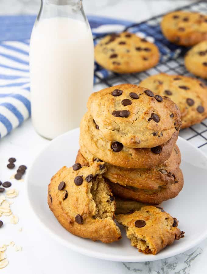 Vegane Kekse auf einem weißen Teller mit einem Blech mit Keksen und einer Flasche Milch im Hintergrund