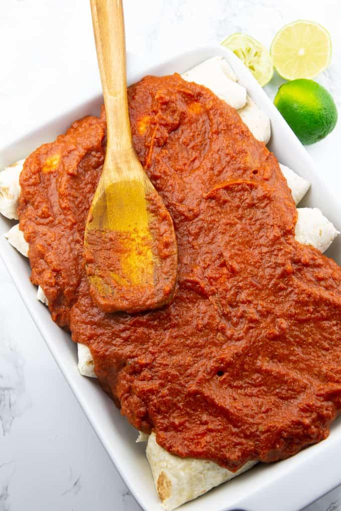 Enchilada Sauce wird mit einem Holzlöffel auf Enchiladas in einer weißen Auflaufform verteilt