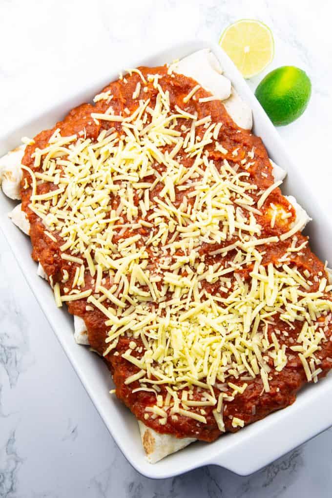 Enchiladas mit veganem Streukäse in einer weißen Auflaufform auf einer Marmorplatte vor dem Backen