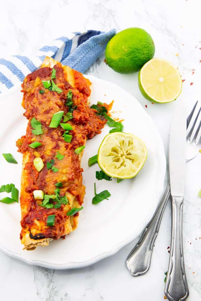 Enchiladas auf einem weißen Teller auf einer Marmorplatte mit Besteck daneben und Limetten im Hintergrund