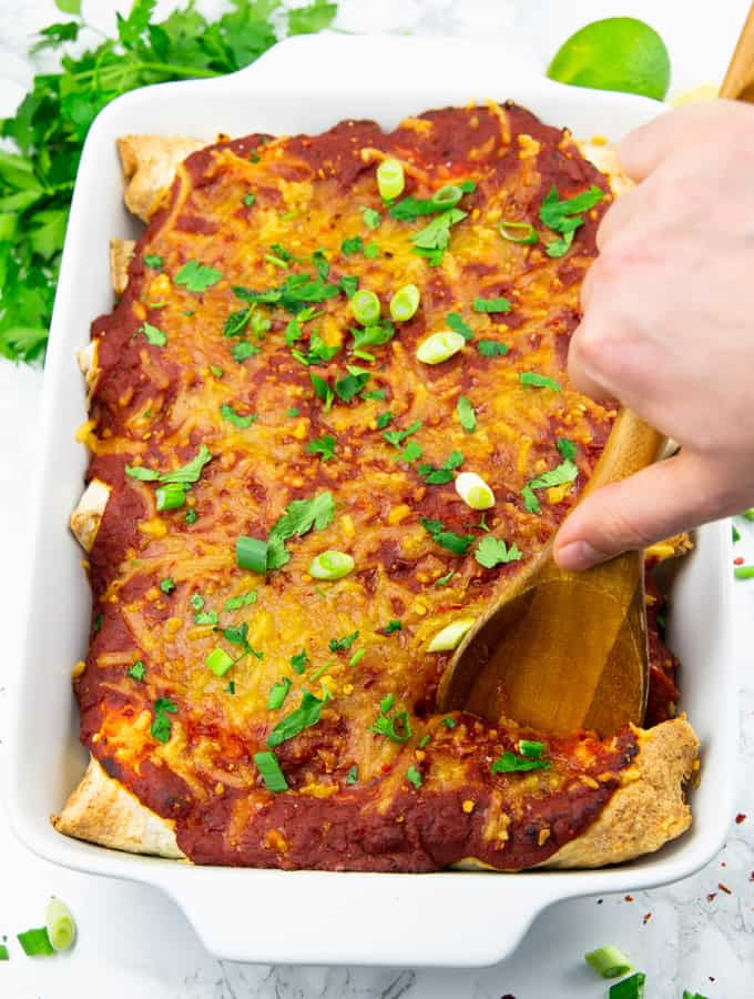 Enchiladas in einer weißen Auflaufform mit einer Hand mit einem Holzlöffel