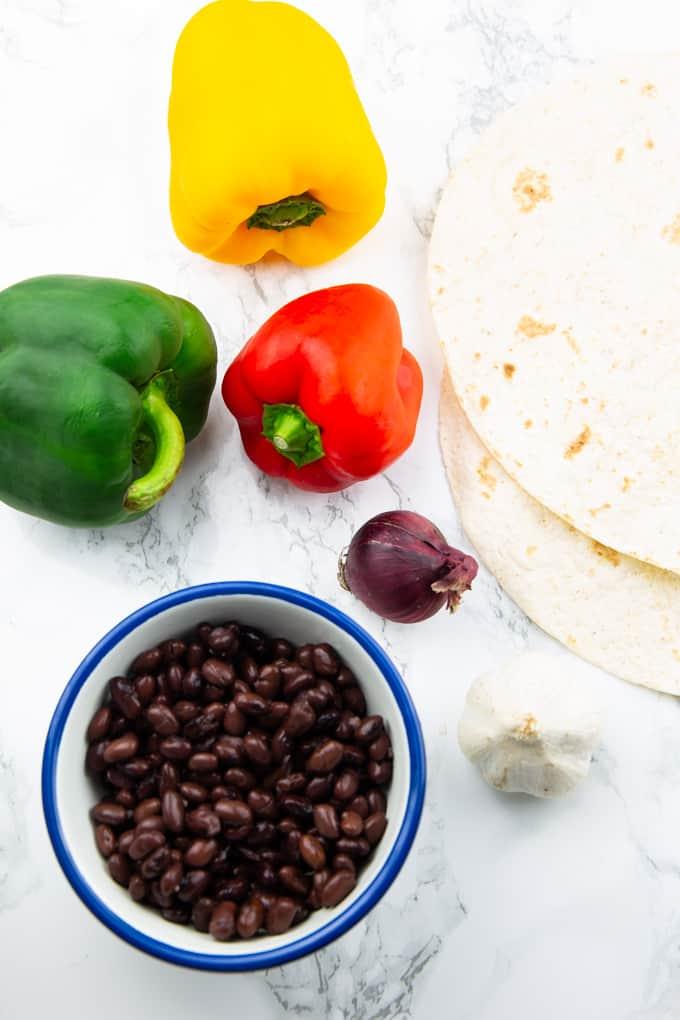 drei Paprika, eine rote Zwiebel, Knoblauch, eine Schüssel mit schwarzen Bohnen und zwei Tortillas auf einer Marmorplatte