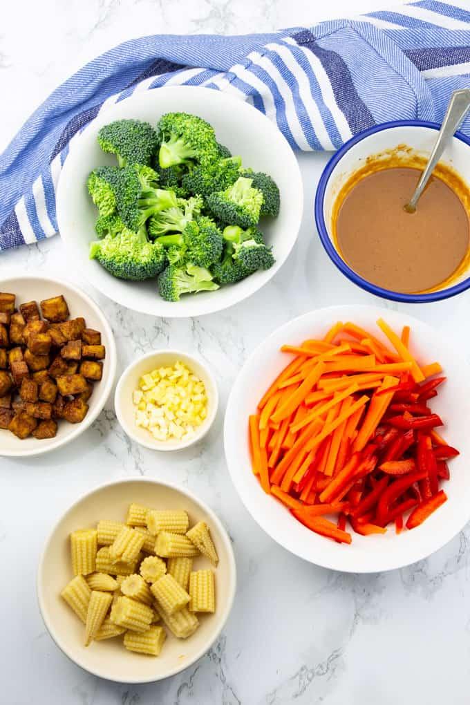 Zutaten für Pad Thai in Schüsseln auf einer Marmorplatte (Tofuwürfel, Brokkoli, Paprika, Karotten, Maiskolben und Erdnusssauce)