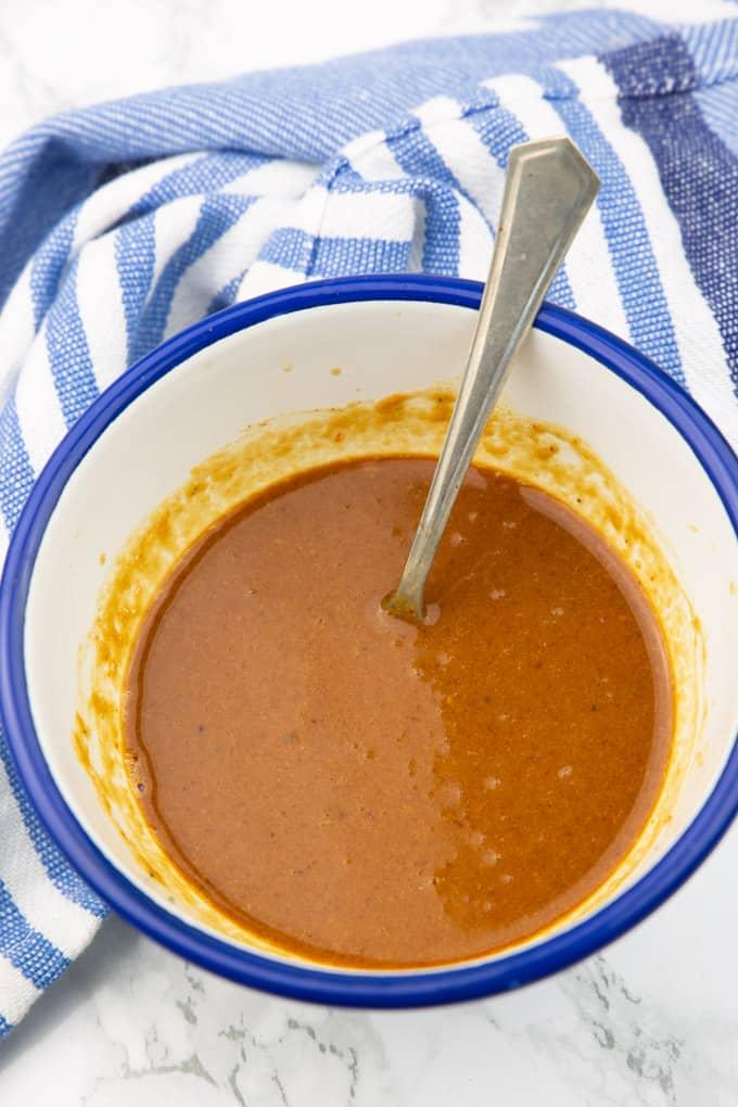 Pad Thai Sauce in einer weiß blauen Schüssel mit einem kleinen Löffel auf einer Marmorplatte