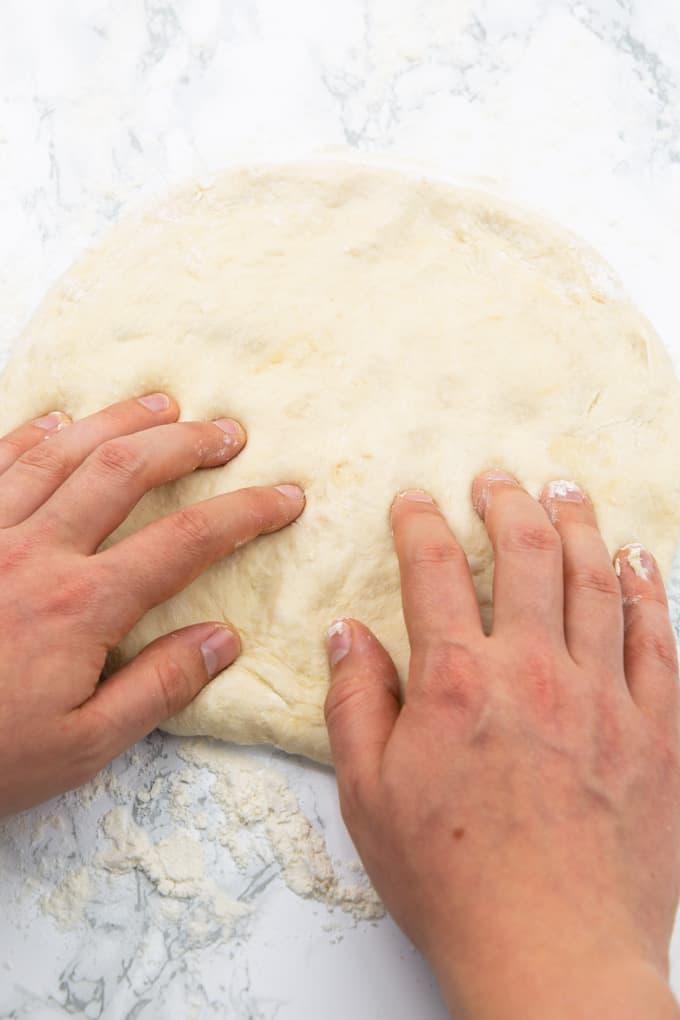 selbst gemachter Pizzateig wird auf einer mit Mehl bestreuen Marmorplatte mit den Händen geknetet