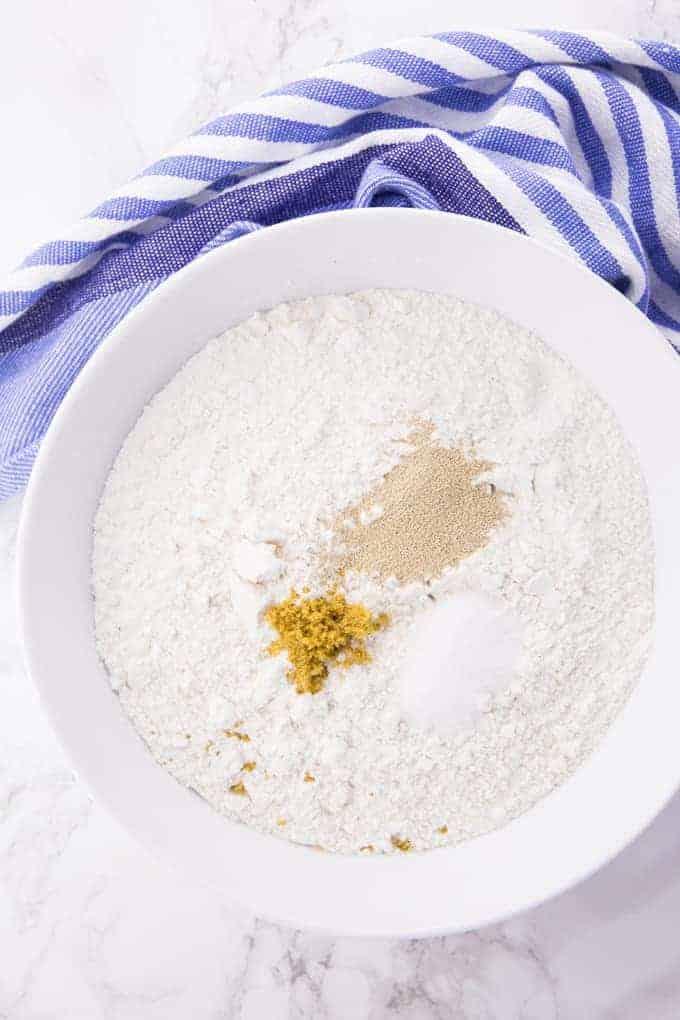 trockene Zutaten für Pizzateig in einer weißen Schüssel auf einer Marmorplatte