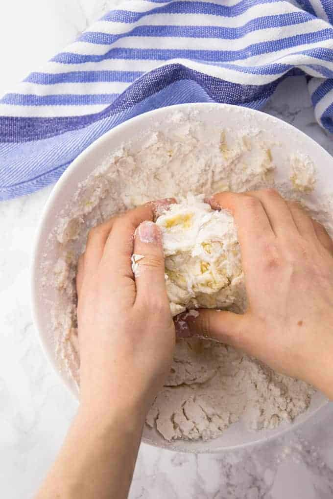 Selbst gemachter Pizzateig wird in einer weißen Schüssel mit den Händen geknetet