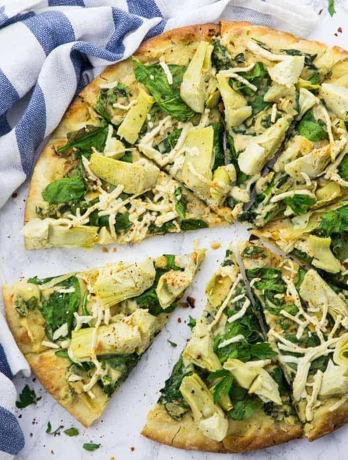 vegane Pizza mit Spinat und Artischocken auf einer Marmorplatte mit einem blau weißen Küchentuch im Hintergrund