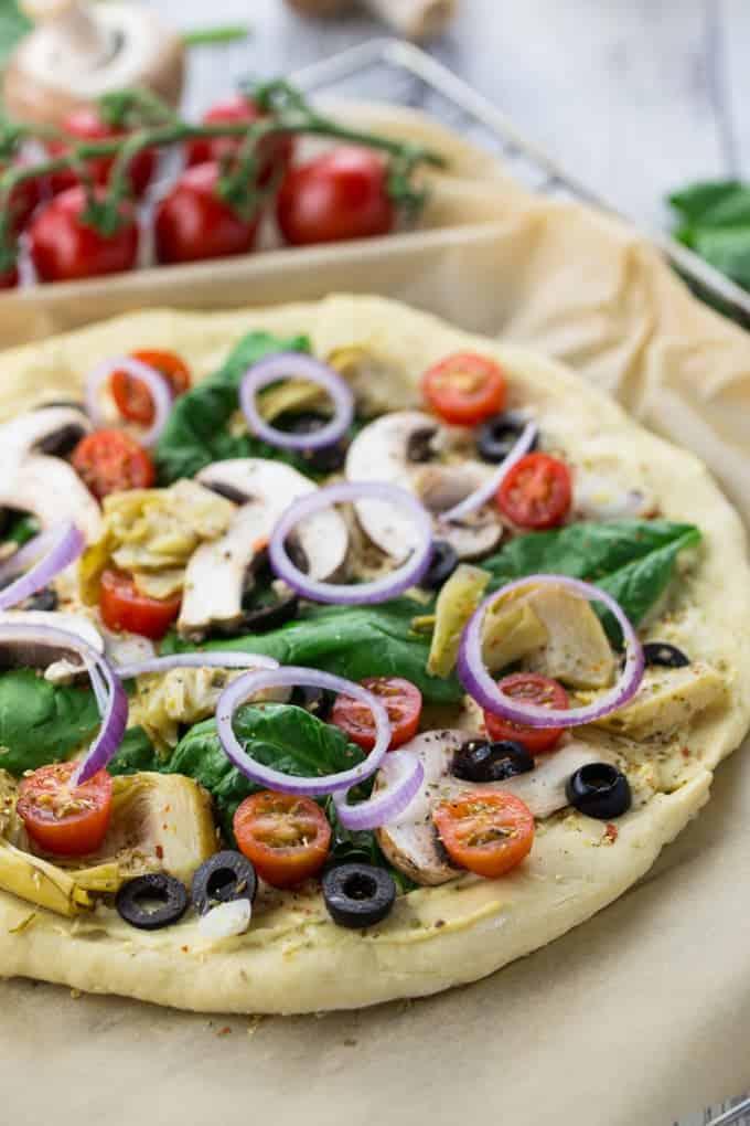 frischer Pizzateig mit Hummus, Spinat, Champignons, Oliven und Tomaten auf einem mit Backpapier belegten Backblech