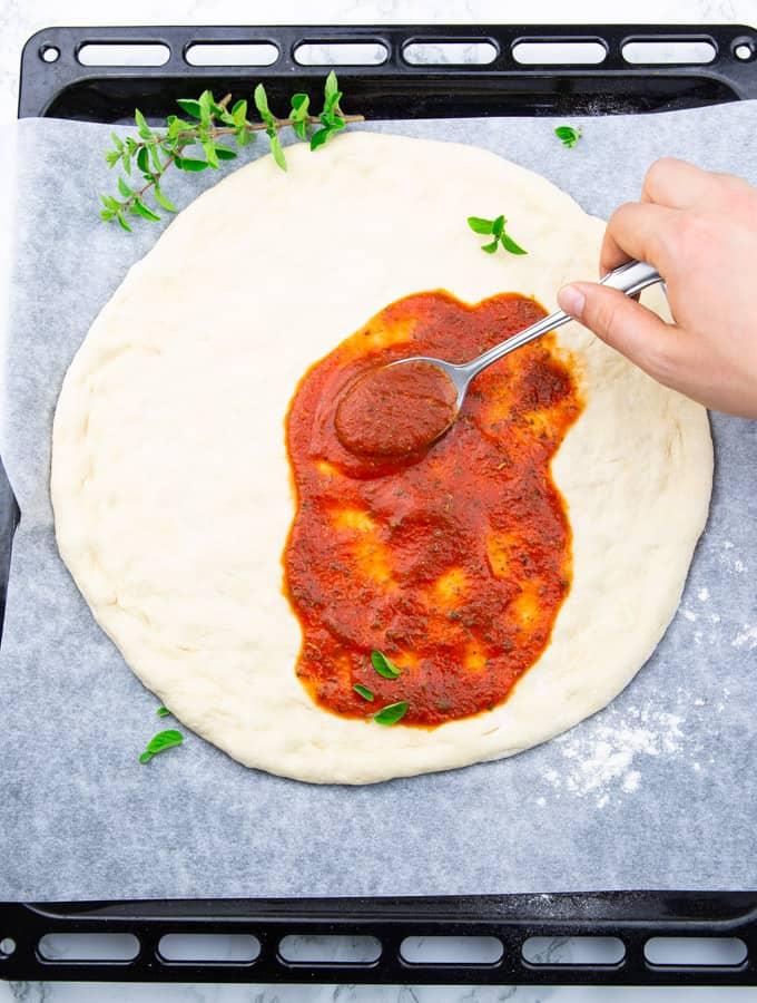 selbst gemachter Pizzateig auf einem mit Backpapier ausgelegten Backblech, das mit Tomatensauce bestrichen wird