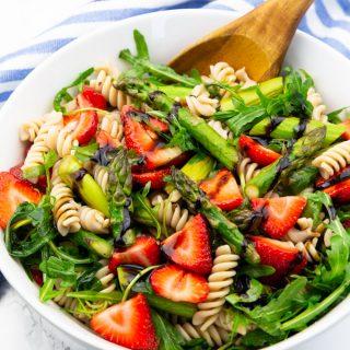 Spargel Erdbeer Salat in einer weißen Schüssel mit einem Holzlöffel auf einer Marmorarbeitsplatte