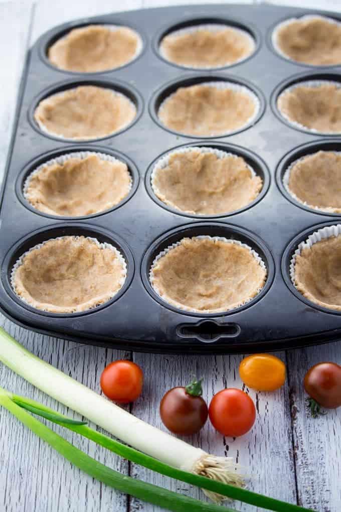 Ein Muffinblech mit Teig für vegane Quiche vor dem Backen