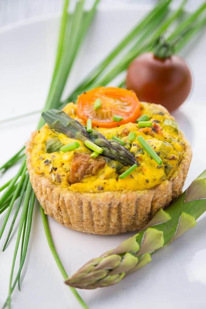 eine vegane Quiche auf einem weißen Teller mit einer Stange grünem Spargel, einer Kirschtomate und Schnittlauch im Hintergrund