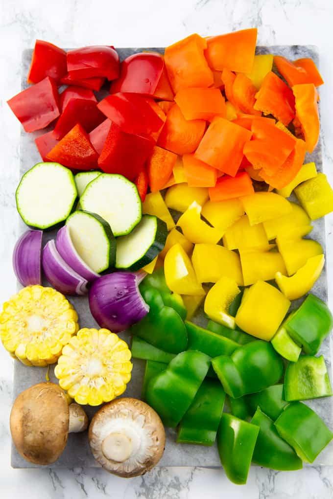 Paprika, Zucchini, Maiskolben, rote Zwiebeln und Champignons in gleich große Stücke geschnitten