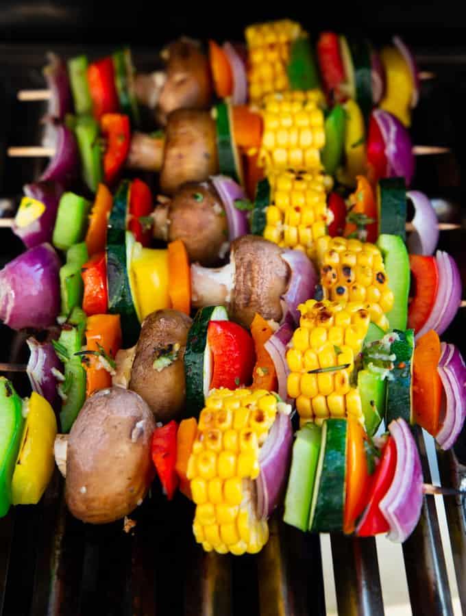 Sechs vegane Gemüsespieße auf einem Grill