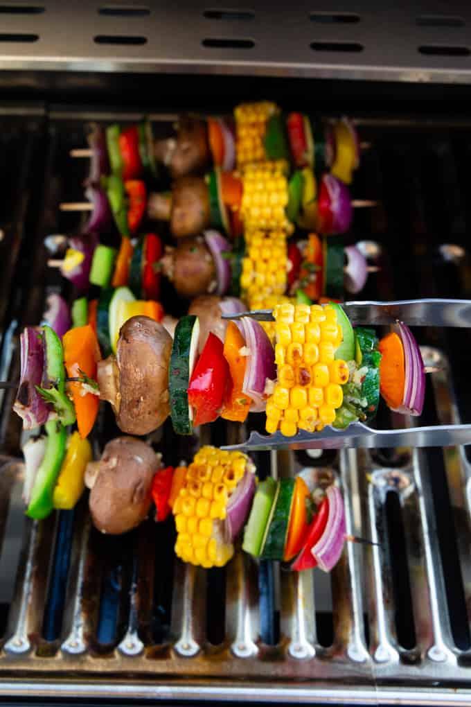 Sechs Gemüsespieße auf dem Grill, ein Spieß wird mit einer Grillzange gewendet