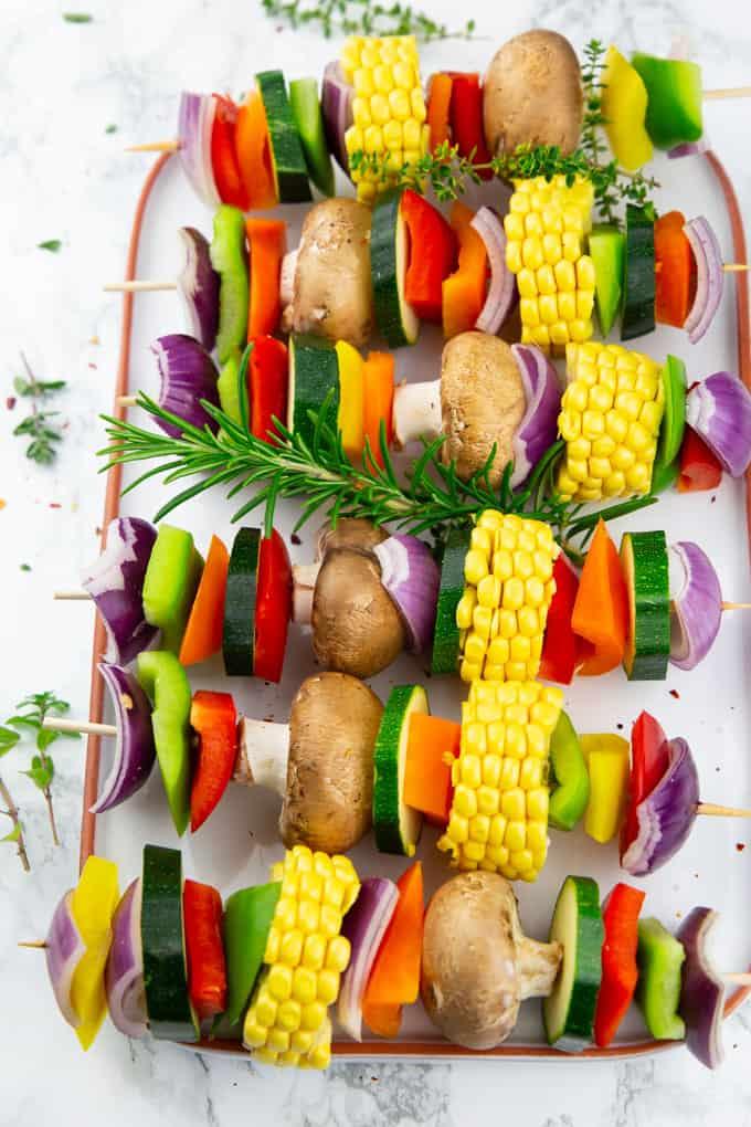Gemüsespieße auf einem weißen Servierteller vor dem Grillen