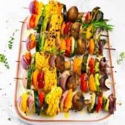 Sechs gegrillte Gemüsespieße auf einem weißen Servierteller bestreut mit frischen Kräutern