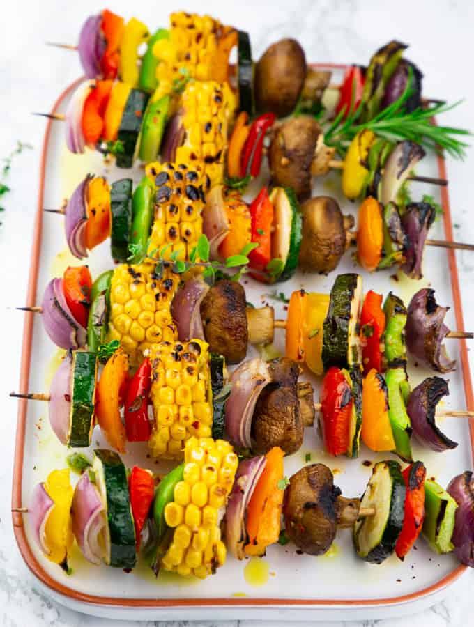 Sechs gegrillte Gemüsespieße auf einem weißen Servierteller