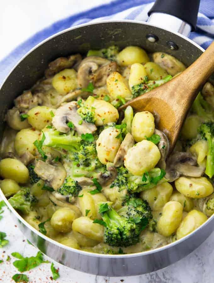 Gnocchi Pfanne mit Brokkoli und Pilzen und einem Löffel aus Holz