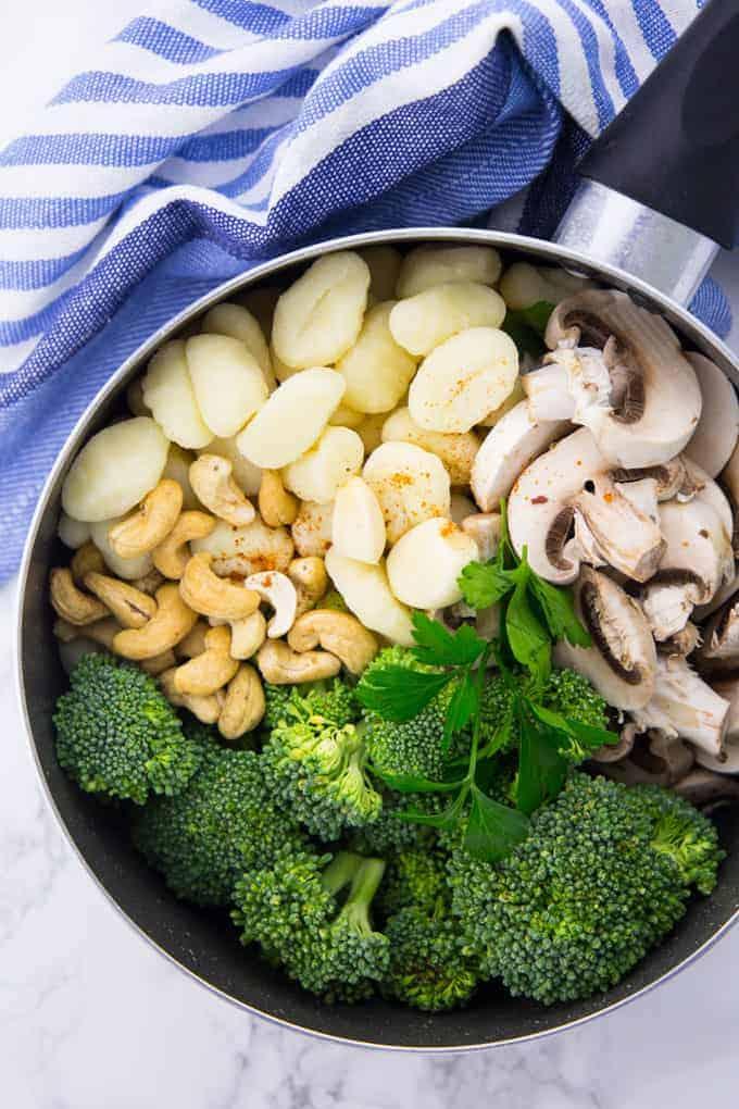 Die Zutaten für die Gnocchi Pfanne in einem Topf: Ungekochte Gnocchi, Pilze, Brokkoli, Cashews und Petersilie
